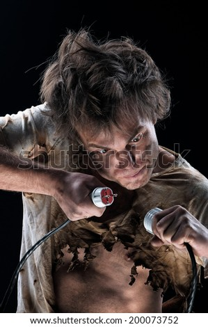 Portrait of funny electrician over black background - stock photo