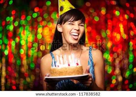 Portrait of funny girl with birthday cake grimacing and looking at camera at party
