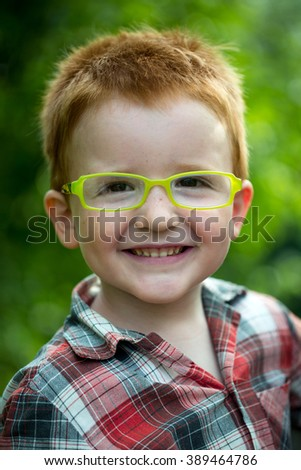 Portrait of funny happy smiling cute little boy with red hair in checkered shirt and yellow glasses sunny day outdoor on blurred natural background, vertical picture - stock photo