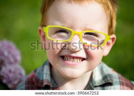 Portrait of funny happy smiling cute little boy with red hair in checkered shirt and yellow glasses sunny day outdoor on blurred natural background, horizontal picture - stock photo