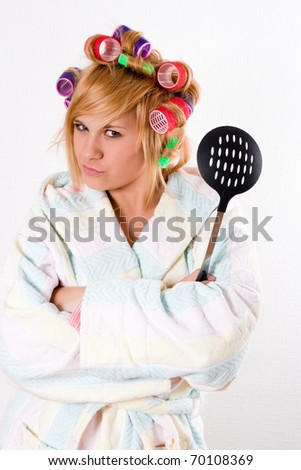 portrait of funny housewife with curlers and skimmer - stock photo