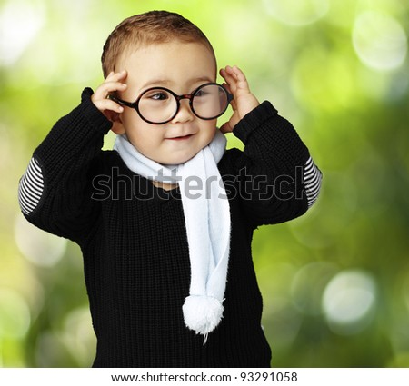 portrait of funny kid holding his glasses  against a nature back - stock photo