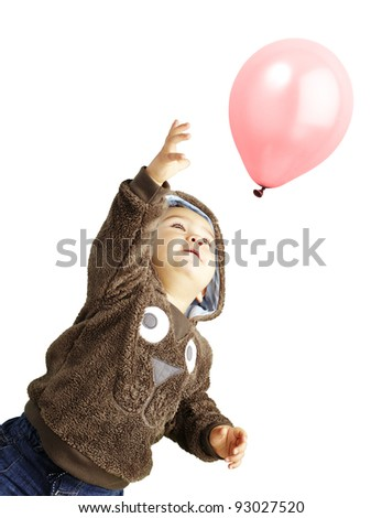 portrait of funny kid trying to hold a pink balloon over white background - stock photo