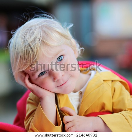 Portrait of funny little child, adorable blonde toddler girl in warm yellow coat outdoors - stock photo