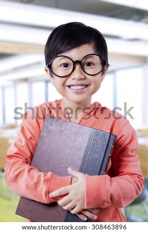 Portrait of funny little student wearing glasses and smiling on the camera while holding a book in class - stock photo