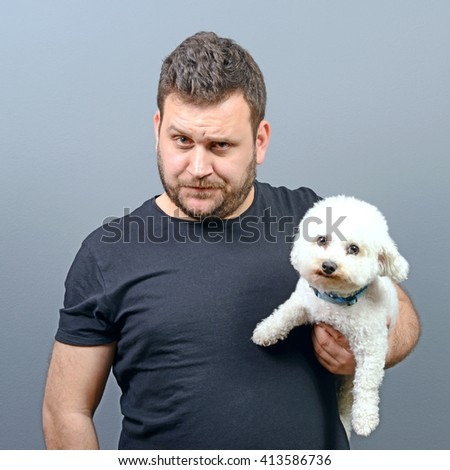 Portrait of funny looking chubby man holding cute small Bichon Frise puppy against gray background - stock photo