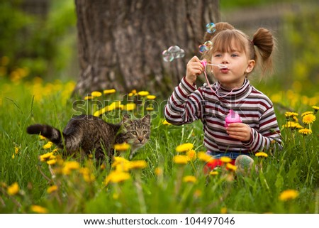 Portrait of funny lovely little girl and a cat, blowing soap bubbles - stock photo