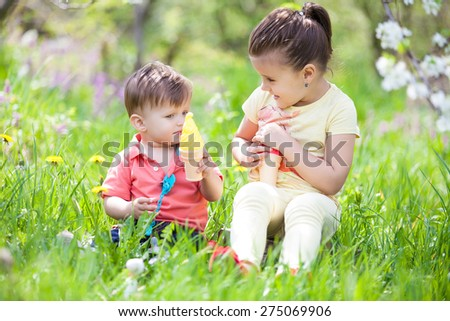 Portrait of funny lovely little girl and boy blowing soap bubbles