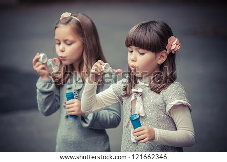 Portrait of funny lovely little girls blowing soap bubble - stock photo