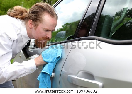 Portrait of funny man washing car with a cloth - stock photo