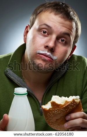 Portrait of funny man with bread and bottle. Yogurt traces on his lips - stock photo
