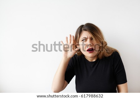 Portrait of funny plus size young woman looking aside holding hand to her ear and trying to hear something standing on white background. Cute Caucasian female with a hearing disorder or hearing loss.