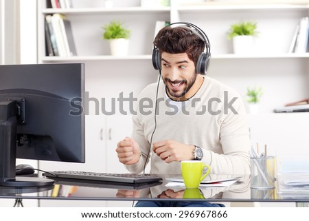 Portrait of funny professional with headphone sitting at workplace. Young creative designer working at studio while download music from internet at office.  - stock photo