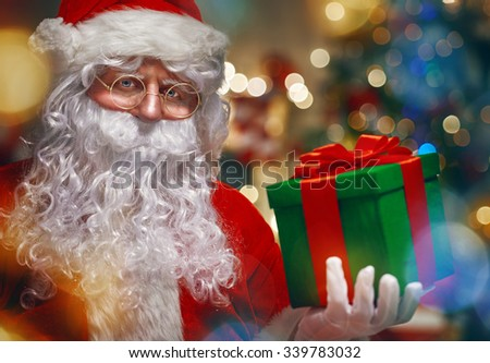 Portrait of funny Santa Claus with christmas gift - stock photo