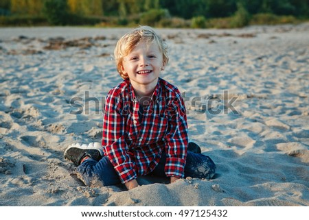 Portrait of funny smiling laughing white Caucasian child kid blond boy, sitting playing with sand on beach at sunset, looking at camera, happy lifestyle childhood concept