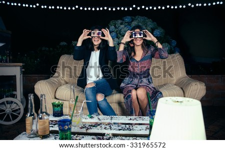 Portrait of funny young women couple holding smartphones over their faces showing male eyes in the screen on a outdoors party. Friendship and celebrations concept. - stock photo