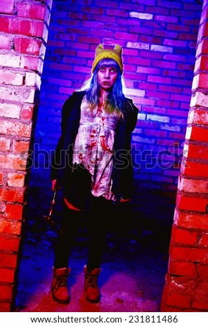 Portrait of funny zombie girl in halloween time with hammer - stock photo