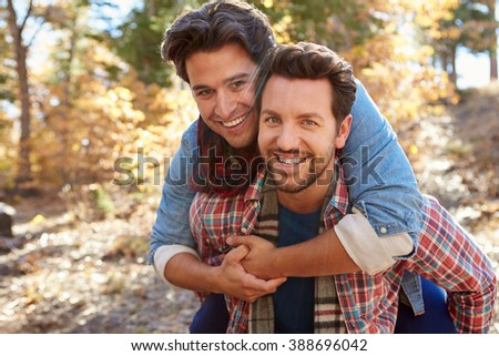 Portrait Of Gay Male Couple Walking Through Fall Woodland - stock photo