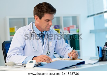 Portrait of general practitioner writing in notebook when sitting at his workplace