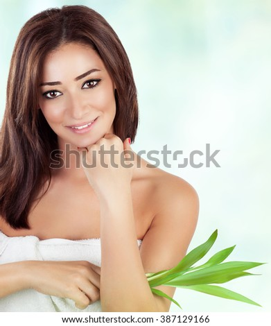 Portrait of gentle female holding fresh green leaves over blur and white background, with pleasure spending day in luxury spa salon - stock photo