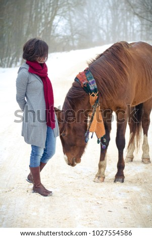 portrait of girl and red trakehner stallion horse with scarf in the winter