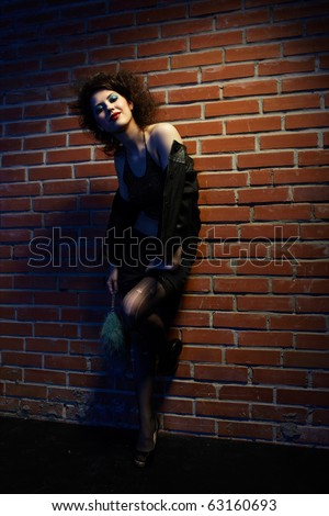 portrait of girl dressed like hooker posing near brick wall