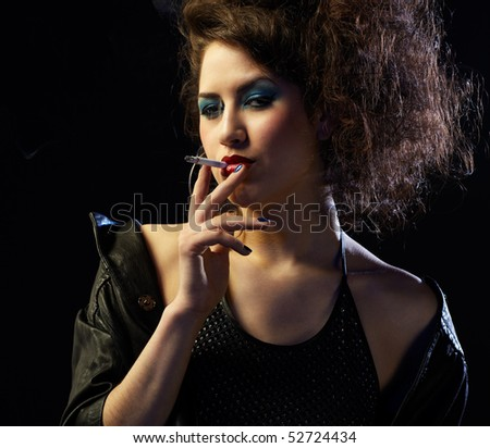 portrait of girl dressed like hooker smoking on black - stock photo