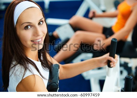 portrait of girl exercising in gym. other girl on multi gym out of focus on background. - stock photo