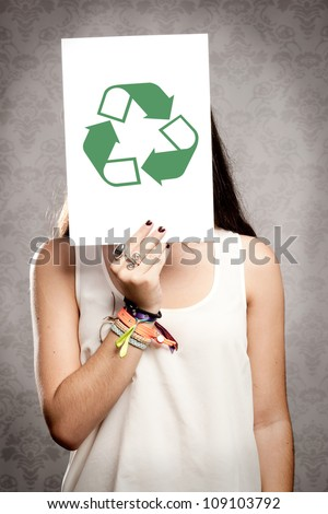 portrait of girl holding a recycling symbol in front of her face
