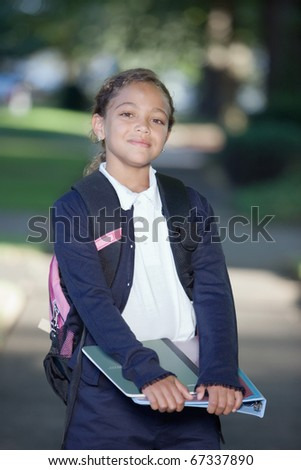 Portrait of girl holding school books - stock photo