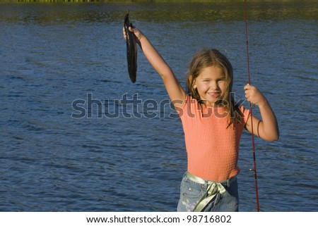 Portrait of girl holding up fish and fishing pole - stock photo