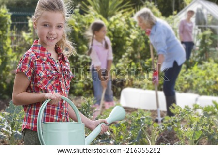 Portrait of girl holding watering can in garden