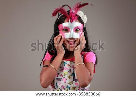 Portrait of girl holds a samba mask on face - stock photo