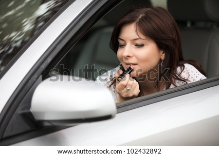 Portrait of  girl in a mirror of car of a painting lip - stock photo