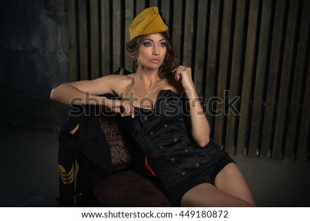 portrait of girl in a sexy black aviator uniform with hat - stock photo