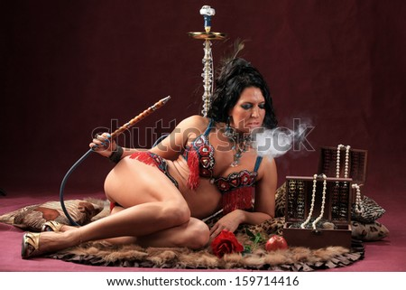 portrait of girl in beautiful clothes east smokes hookah lying on furs on burgundy background studio
