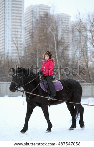 Portrait of girl in winter clothes on a black horse at the equestrian site in front of trees and buildings
