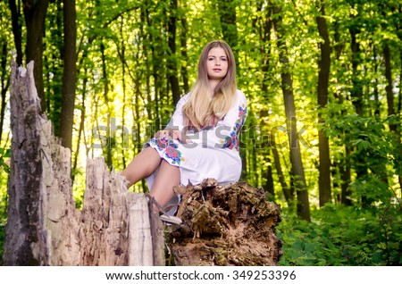 Portrait of girl sitting on tree stump in forest