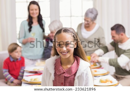 Portrait of girl smiling at camera in front of her family at home in the living room - stock photo
