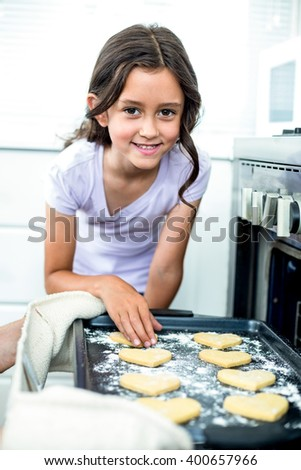 Portrait of girl smiling while touching heart shape cookies in tray by oven - stock photo