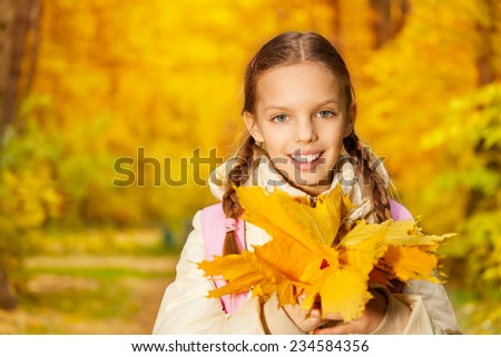 Portrait of girl with autumn yellow leaves bunch - stock photo
