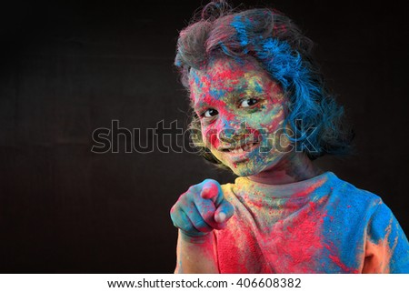 Portrait of girl with face smeared with colored powder points her finger in a dark background. Concept for Indian festival Holi. - stock photo