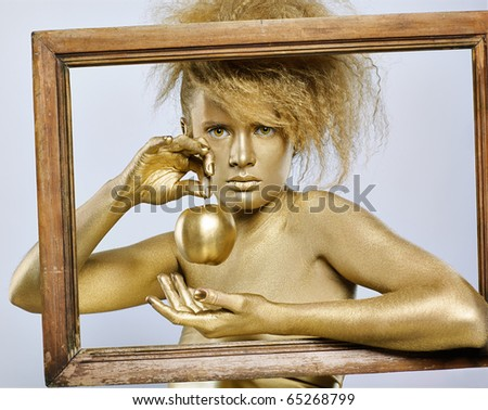 portrait of girl with golden bodyart posing with golden apple in her hands in picture frame on gray