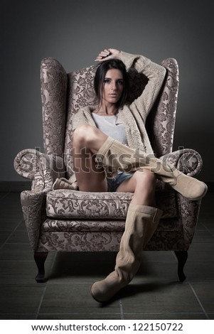 Portrait of girl with old chair and serious face - stock photo