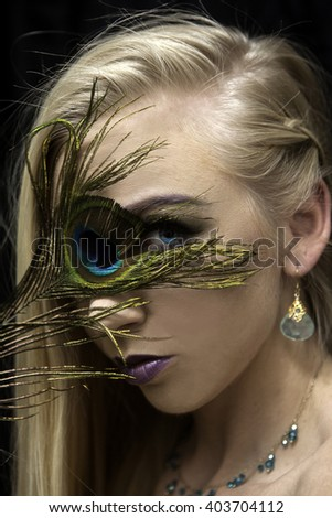 portrait of girl with peacock feather - stock photo