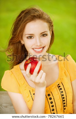 Portrait of girl with red apple against green grass. - stock photo