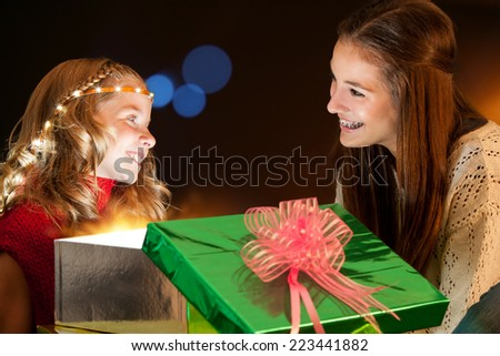 Portrait of Girls  sharing quality time opening Christmas presents. - stock photo