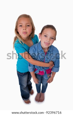 Portrait of girls sticking out their tongues against a white background - stock photo