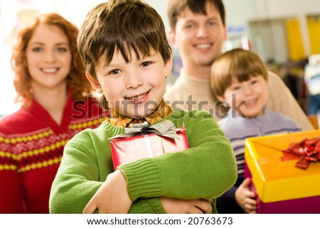 Portrait of glad boy with present looking at camera on background of family members - stock photo