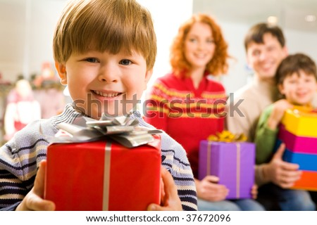 Portrait of glad boy with present looking at camera on background of family members
